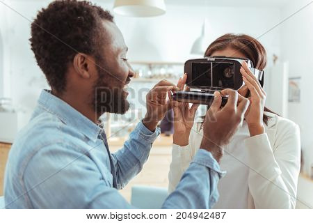 All set. Pleasant young man putting the smartphone inside in the VR headset of his best friend while the woman wearing it, being ready to use it