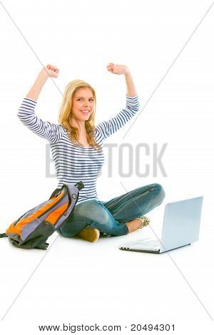 Sitting on floor with schoolbag and laptop pleased teengirl rejoicing her success isolated on white