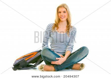 Smiling young girl with schoolbag sitting on floor isolated on white