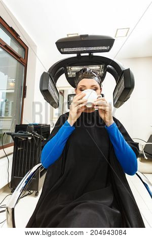 Haircare relaxation and hairstyling concept. Woman sitting in black cape getting her hair dried under machine drinking a cup of tea
