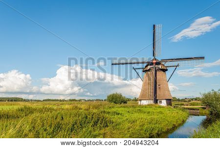 The eight-sided thatched windmill De Oude Doorn near the Dutch village of Almkerk was built around 1700 and restored in 2012. It is a sunny day in the late summer season.