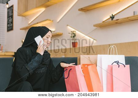 happy muslim woman talking by phone with shopping bags in cafe