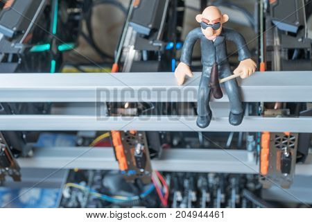 Bald plasticine man with a pickaxe mines cryptocurrency sitting on mining farm