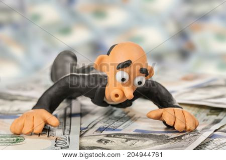 Surprised bald plasticine businessman lies on a pile of hundred dollar bills