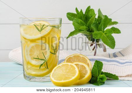Summer fruit drink on wooden background. Cold lemonade with ice. Detox citrus infused flavored water. Refreshing summer homemade cocktail with lemon. Fresh lemon and lemonade