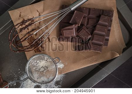 Chocolate on egg beater and chocolate parts on wooden table top.