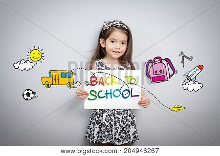 Back to school concept: Cheerful smiling little girl hold paper write back to school with colorful with cartoon around. Cute mixed race girl half Thai half English model 3 years old.