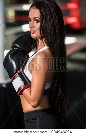 Portrait of a woman boxer aggressive and ready to fight. girl in boxing gloves posing in boxing hall
