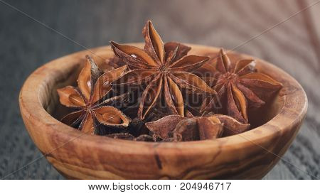 anise stars in olive bowl on oak table, rustic style