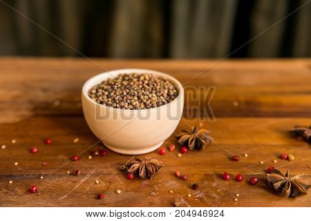 Close up coriander seeds in white bowl on wooden table covered with anise and pink peppercorn