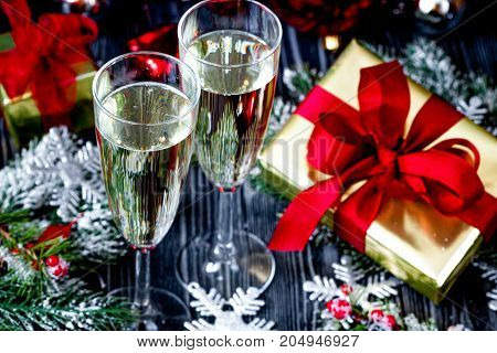 glasses of champagne and Christmas ornaments on dark wooden background.