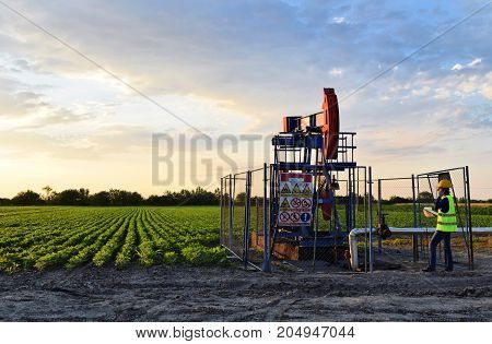A female engineer on an European oil well during dusk time