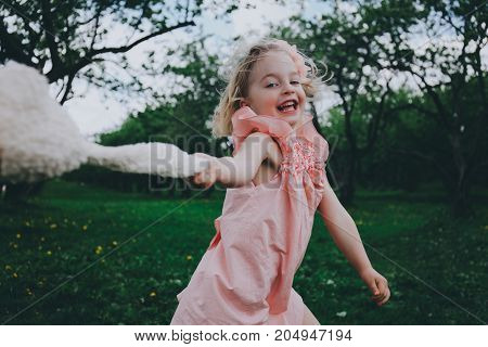 Little cute girl in a pink dress running on the grass with toy rabbit.