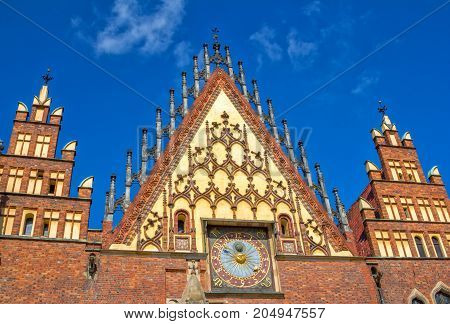 Wroclaw/Poland- August 17, 2017: Market Square - part  view of beautiful  gothic old Town Hall with ornaments and clock over blue sky