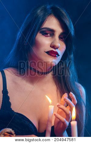 Beautiful witch with Halloween pumpkins over blue smoky background with backlight