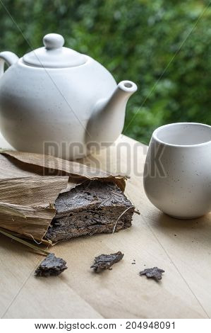 Natural tea with white teakettle and cup on the wooden table and green leaves as background