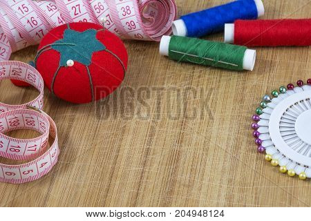 Red pincushion, tape and colourful threads with needle are on the light wooden background