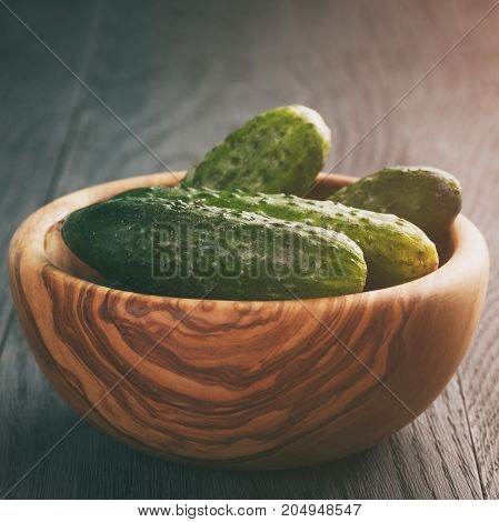 whole cucumbers in olive dowl on old wood table