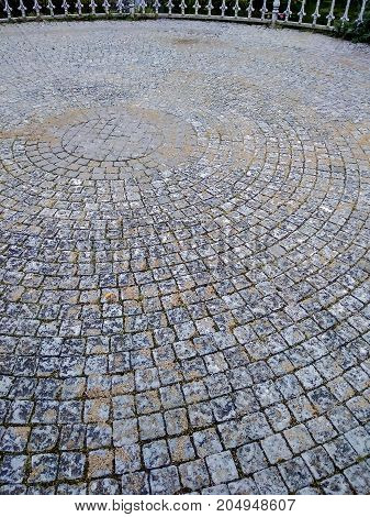 Abstract background of old cobblestone pavement at city park.
