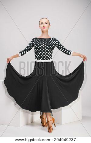pretty woman in polka-dot dress in studio, dancer posing in beatiful suit