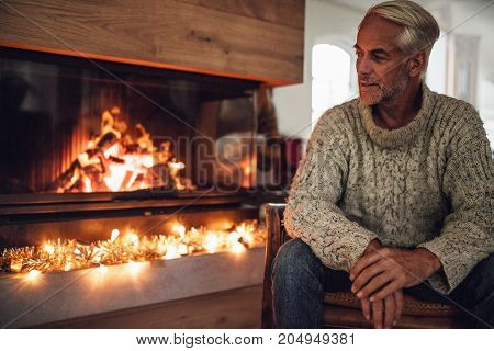 Mature man sitting by fire place in living room at home. Senior male relaxing on chair.