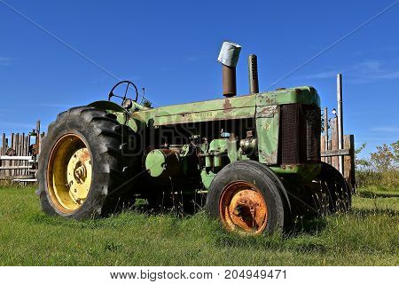 DOWNER, MINNESOTA, September 17, 2017: The old green tractor with a pail over the muffler is a product of John Deere Co, an American corporation that manufactures agricultural, construction, forestry machinery, diesel engines, and drivetrains.