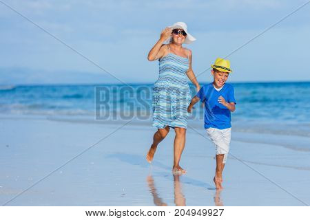 Little cute boy with his mother having fun at the white sand beach