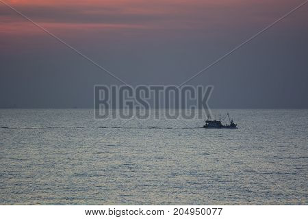 Silhouette of fishing boat in the ocean at sunset.