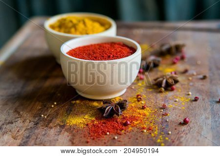 Close up two bowls filled with red paprika and yellow turmeric powder on dark wooden table covered with anise