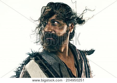 Portrait of a brutal bald-headed viking in a battle isolated against a white background. Early medieval period. Actor in makeup. concept of vagrancy and survival