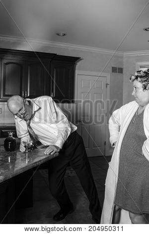 Drunk Man With Wife In Kitchen In Black And White