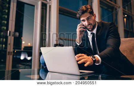 Businessman At Airport Waiting Lounge Using Laptop And Mobile Ph
