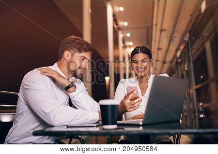 Young woman and man sitting at cafe with laptop and mobile phone. Happy business people waiting for flight at airport cafe.