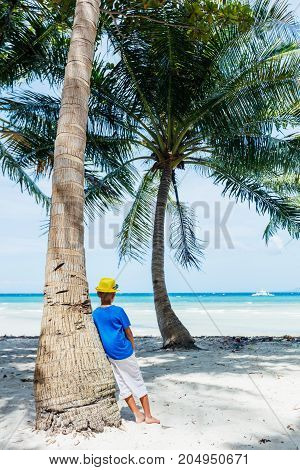 Young happy boy having fun on a white sand tropical beach with palms tree