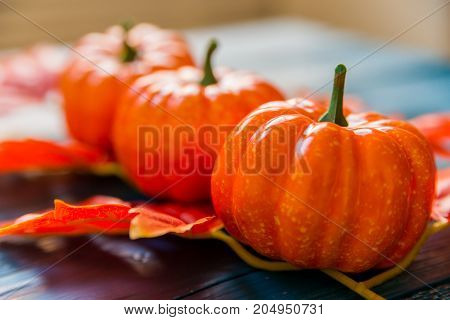 Close up three artificial pumpkins and maple leaves on blue wooden background autumn concept