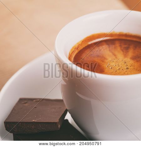 freshly made espresso shot with chocolate, on wooden table
