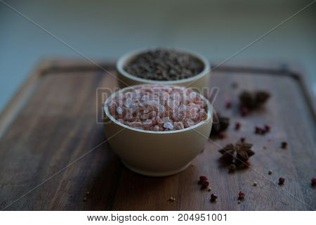 Pink Himalayan salt and coriander seeds in white bowls on wooden surface covered with anise and red peppercorn