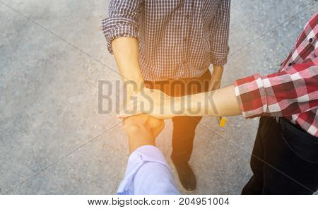 Three Engineer men putting handshake teamwork or partner building success project in side construction copy space the left