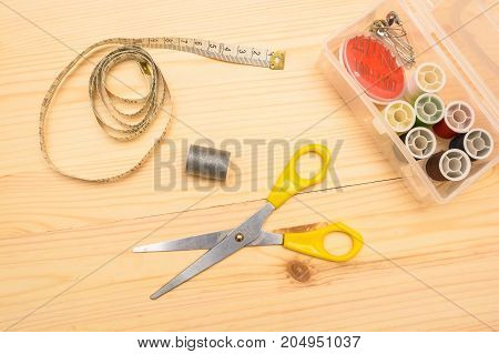 Top view sewing kit of scissors, thread, measuring tape on wooden table