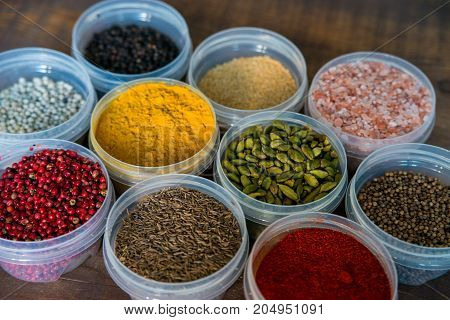 Close up image of several plastic bowls filled with different bright colorful spices and salt