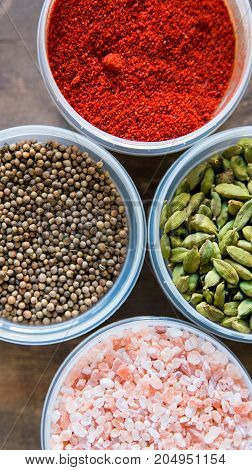 Top view image of several plastic bowls filled with different bright colorful spices and salt