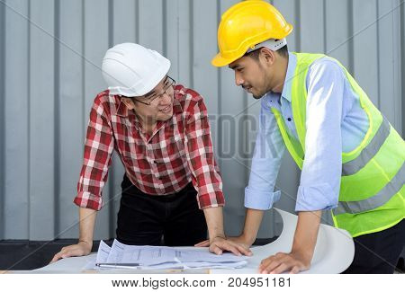 Engineer men with safety helmet working teamwork building consult project in side construction in industy with paper plan on table