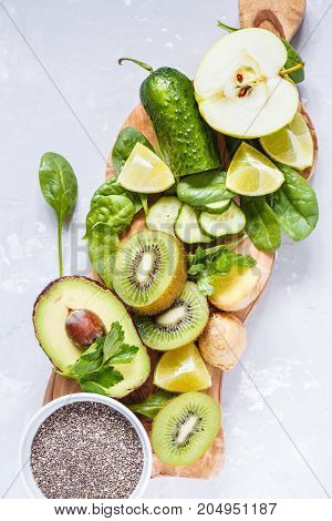 Ingredients for green detox smoothies (juice) vegetables and berries on a wooden board top view. Space for text.