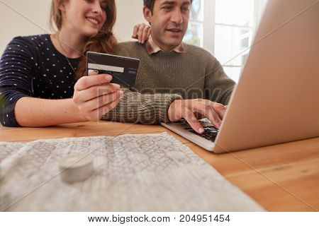 Young man and woman shopping online with credit card at home focus on credit card. Couple buying on internet.