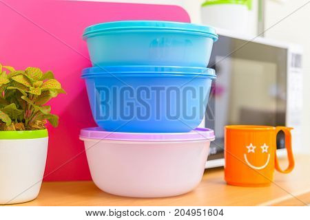 Close up of modern bright colorful food containers on kitchen table