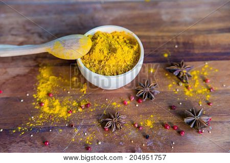 Close up bright turmeric powder in white bowl with wooden spoon and anise and pink peppercorn