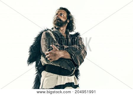 Actor in makeup, a poor man isolated on white studio background. The bum in canvas rags. concept of vagrancy and survival