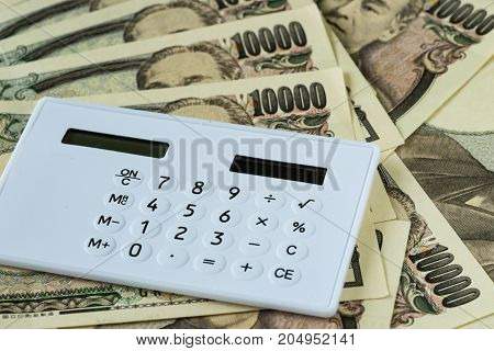 Calculator on pile of japanese yen banknotes as financial safe haven or tax concept.