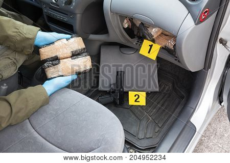 Policeman holding drug packages discovered in secret compartment of the car
