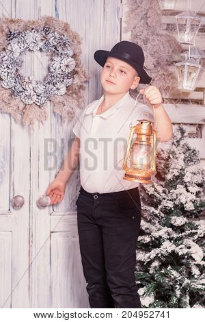 A 10 years boy staying at dorstep and holding lantern in his hand at Christmas